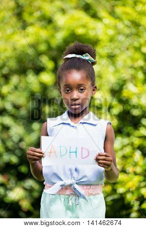 Cute mixed-race girl holding a paper with a message on a park