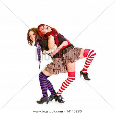 Two cheerful girlfriends standing back to back and funny posing together isolated on white