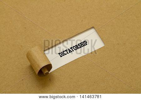 DICTATORSHIP word written under torn paper .