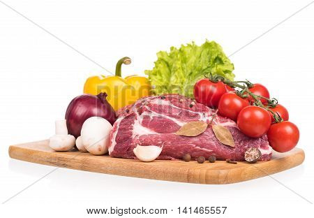 Raw pork with spices and vegetables on the chopping board over white background