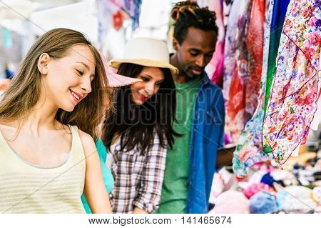 Multi-ethnic best friends choosing clothes at the weekly cloth market - Young people sharing free time and having fun in the old town - Vacation and shopping concept - Soft vivid filter
