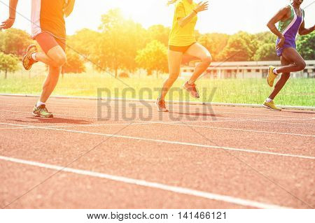 Multi-ethnic athletes running on athletic racetrack at sunset - Three runners sprinting for training with back lighting - Sport competition and healthy lifestyle concept - Soft focus on left leg guy