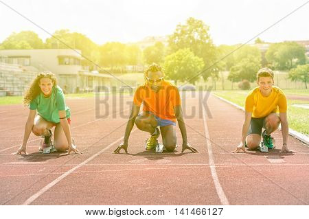 Multiracial runners at start line on track for athletic challenge - Multi ethnic people on starting block with sunshine lights background - Competition sport concept - Focus on black man