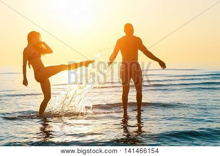 Silhouette of happy couple swimming and playing in water at sunset on beach - Young people having fun on summer time - Vacation and love concept - Main focus on him - Sun original color