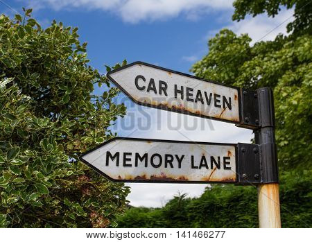 A rusty road sign in the countryside pointing the way to Car Heaven and Memory Lane.