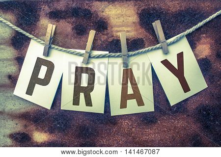 The word PRAY stamped on card stock hanging from old twine and clothes pins over a rusty vintage background.