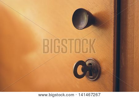 open door of an old wooden cabinet with lock and key