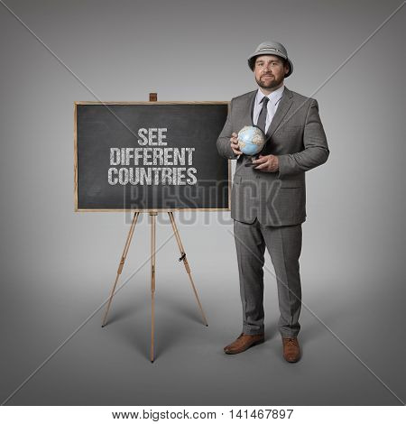See different countries text on blackboard with businessman holding globe in hands