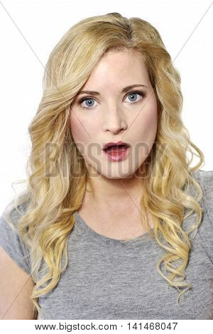 Amazed blond woman looking to the camera. Surprised young woman, isolated on white background.