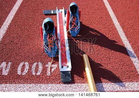 Starting blocks for track and field with spikes set in them and a baton to race with