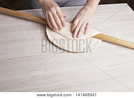 Woman's hands knead dough on a table with rolling pin