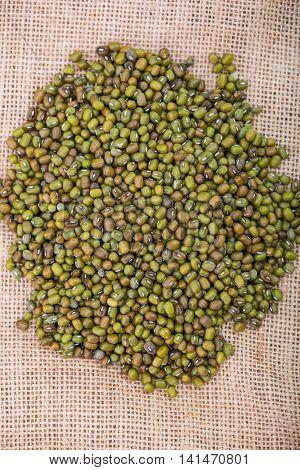 Close up of green mung bean on sack.