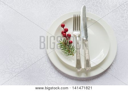 Christmas table in tones of white beautifully served luxurious tableware: porcelain plates and silverware decorated by fir sprig and holly berries; top view