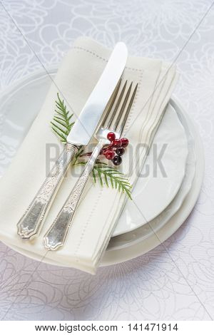 Beautiful Christmas table: silver knife and fork red holly berries and green thuja branches and linen napkin lie on the white porcelain plate which is located on a table covered with a white tablecloth top view