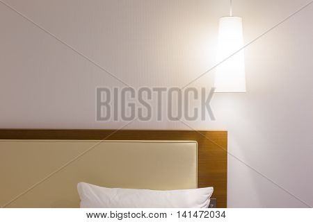 Bed headboard white pillow and over head lamp in simple and minimalist design with room for copy space