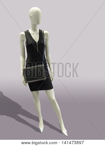Full length black dress mannequin isolated on gray background. No brand names or copyright objects.