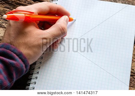 left-handed man writes in a notebook close up