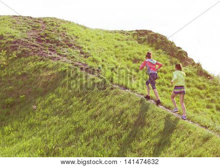 Two fit young women friends exercising in a park running up the hill. Active healthy lifestyle and o