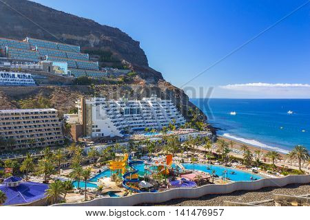TAURITO, GRAN CANARIA, SPAIN - APRIL 23, 2016: Tourists on sun holidays at the Lago Taurito aquapark in Taurito, Gran Canaria. Taurito is very popular tourist destination