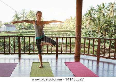 Full length image of fit young woman standing on one leg and meditating at yoga class. Caucasian female doing yoga on exercise mat.