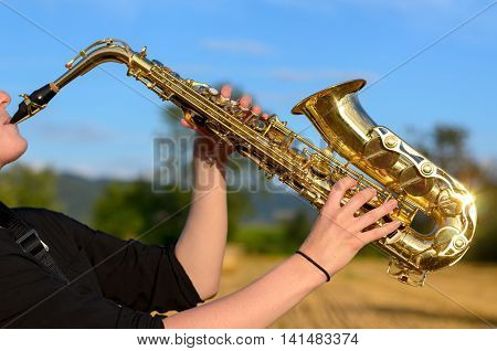 Woman Playing A Tenor Saxophone Outdoors