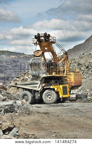Iron ore mining - excavator is loading the dump truck on the opencast