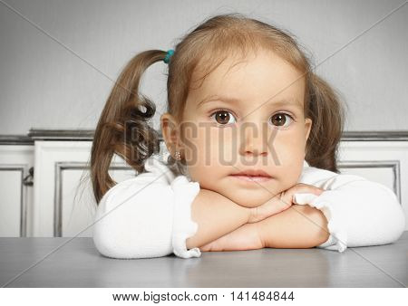 Porteait of serious dreaming child girl in room