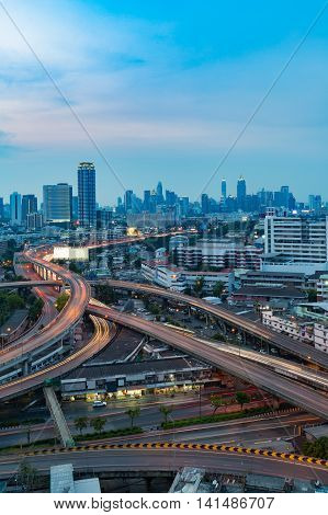 Long exposure, highway interchanged and city downtown background at twilight