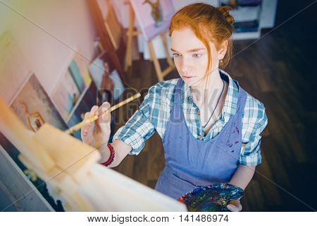 Portrait of concentrated beautiful young woman painter holding art palette and painting on canvas with brush in artist workshop