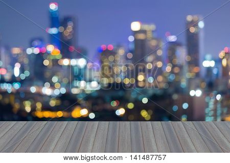 Opening wooden floor, City blur bokeh light during twilight