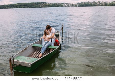 handsome guy and beautiful girl resting in a boat on the lake