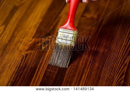 Half painted wooden surface. Deep brown color. Varnishind natural wood with paint brush