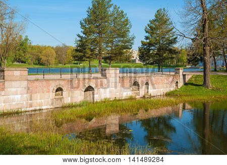 Ancient bridge in the park by the pond