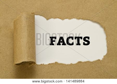 Facts word written on torn paper concept .