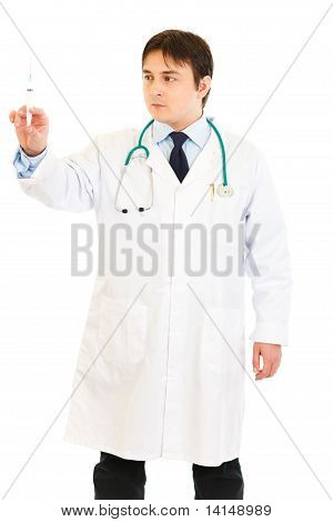 Serious medical doctor holding medical syringe in hand isolated on white