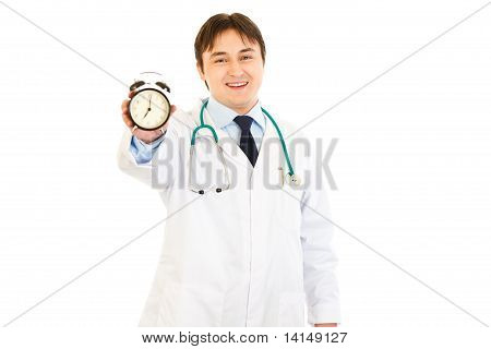 Smiling medical doctor holding alarm clock in hand isolated on white
