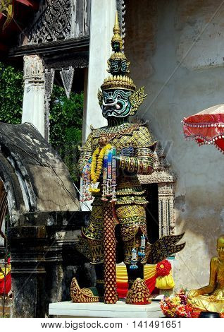 Ayutthaya Thailand - December 21 2010: Green-faced Guardian demon stands at the entrance to the Ubosot sanctuary hall at Wat Tha Ka Rong *