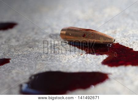 Bullet laying on concrete that has lots of blood around