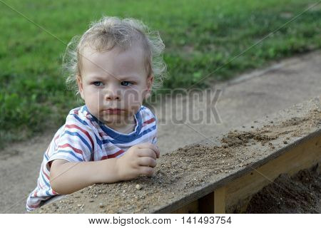 Portrait of a serious toddler in sandbox