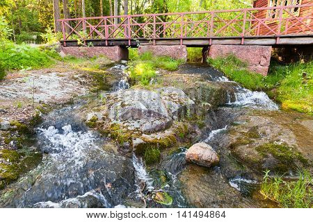 Bridge With Red Railings Over Stream With Waterfall