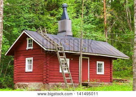 Traditional Scandinavian Red Wooden House In Forest