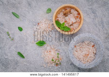 Himalayan Pink Salt In Wooden Bowl With Peppermint ,sage,thyme,basil And Oregano On Stone Background