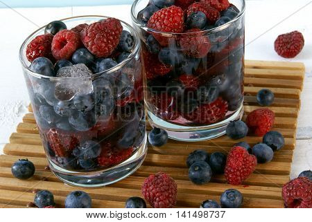 Cooled by ice juicy summer berries in glasses: raspberries, blueberries, bilberries. Rustic white table. Close view.