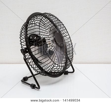 The compact desktop black electric fan on a white background