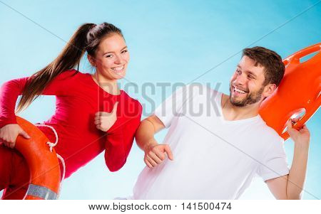 Accident prevention and water rescue. Man and woman lifeguard couple holding buoy lifesaver equipment giving thumb ub hand sign gesture on blue