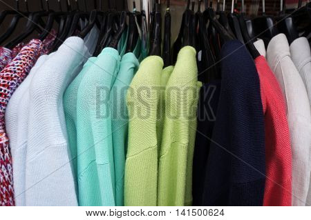 Colorl pullovers on hangers.