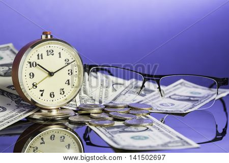 Time is money vintage clock on cash american dollar bills coins and glasses with nice blue background. Business Commerce concept.