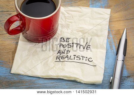 be positive and realistic - handwriting on a napkin with a cup of coffee