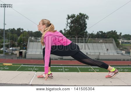 Athlete in black tights lunge stretching over the stadium while looking forward.