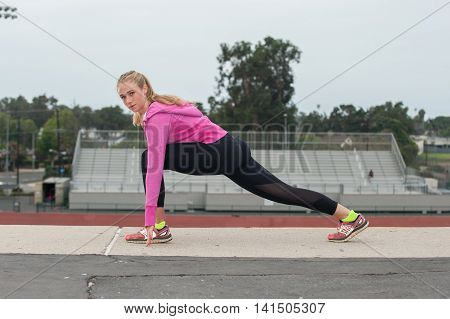 Athlete in black tights lunge stretching over the stadium while looking left.
